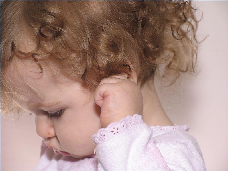 Ребенок трогает ухо к зубам